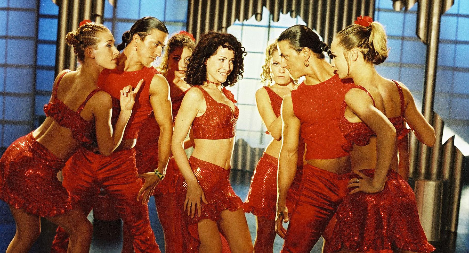 Sandra Pires (Lisa/Maggie Thompson) in Mitten einer Tanzgruppe